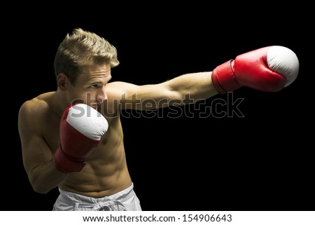 Young boxer fighter performing a punch. Isolated over black background.