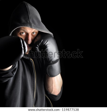 Young boxer in hood isolated on dark background - stock photo