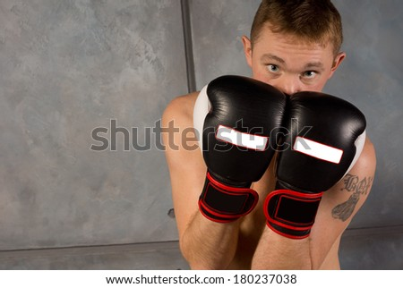 Young boxer protecting his face and head with his gloved fists raised side by side in font of him in a defensive position looking over the top at the camera with copyspace - stock photo
