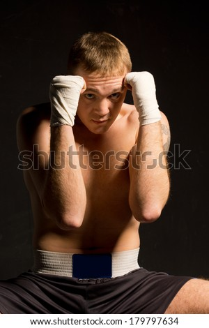 Young boxer protecting his head by raising both his bandaged fists in a defensive position against a dark background - stock photo