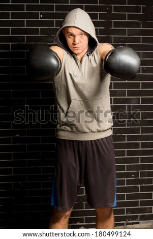 Young boxer punching with both of his gloved fists towards the camera with a look of determination during a workout in a gym - stock photo