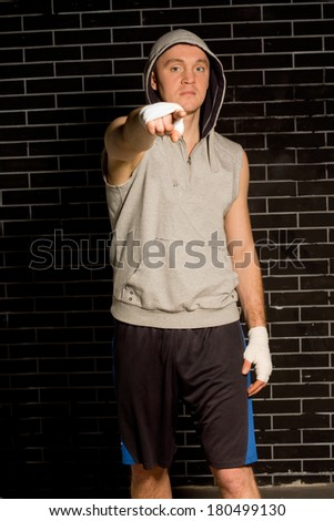 Young boxer standing in darkness against a brick wall pointing at the camera with his bandaged hand as he shows or identifies someone or draws your attention to something - stock photo