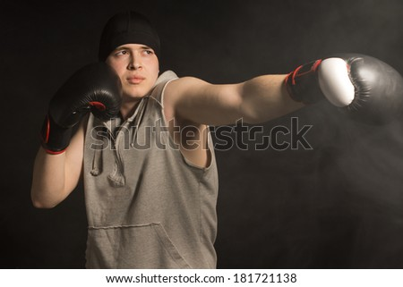 Young boxer throwing a punch with his gloved fist with a look of determined concentration, low angle on a dark background - stock photo