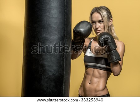 young boxer woman in boxing gloves with punching bag , on black and yellow background, horizontal photo - stock photo