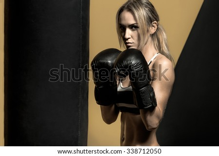 young boxer woman in boxing gloves with punching bag , on black and yellow background, horizontal photo