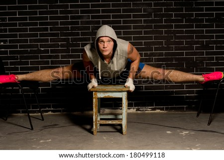 Young boxer working out balancing across three stools with his legs opened in the splits position as he strengthens his muscles and improves suppleness - stock photo