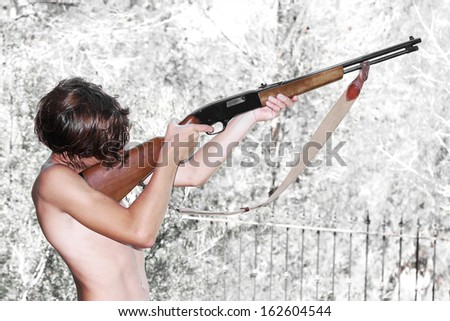 young boy aiming with a rifle - stock photo