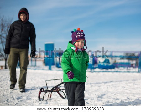 young boy and father sledging in winter park - stock photo