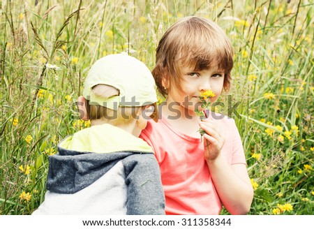 young boy and girl (brother and sister) on the grass with flower - stock photo