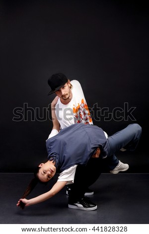 young boy and girl dancer breakdancing and hip hop dancing, posing in creative poses, showing the dance moves of contemporary dance in fashionable clothes for sports on a metal unusual background - stock photo