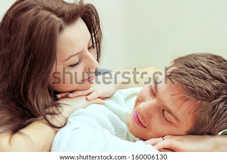 young boy and girl look at each other while lying on bed - stock photo