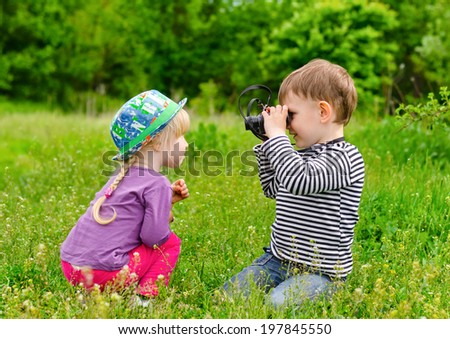 Young boy and girl playing with binoculars in the grass.