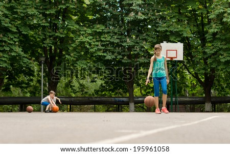 Young boy and girl practising their basketball on an outdoor court bouncing the ball to get into position to shoot at the goal - stock photo