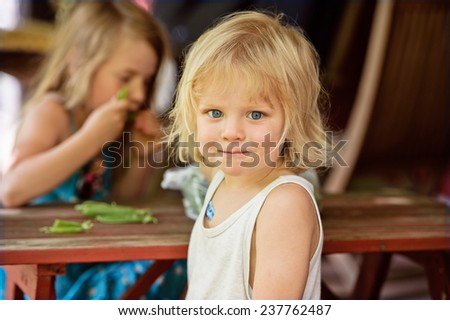 Young boy and girl sit at a red children's table and bench. They are eating peas from the pod. They are lightly dressed in the summer heat The boy smiles with a mouthful of peas.