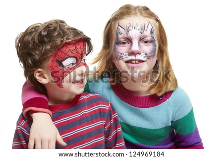 Young boy and girl with face painting of cat and spiderman smiling on white background - stock photo