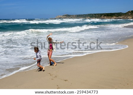 Young boy and woman playing, running, jumping and having fun in the surf on the beach