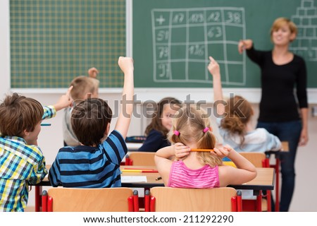Young boy answering a question in class as he sits with his hand raised and a smiling female teacher pointing to him, view from behind - stock photo