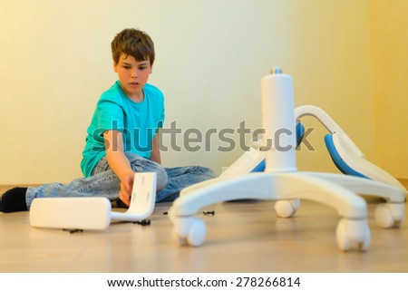 young boy assemble parsed chair in apartment sitting on floor - stock photo
