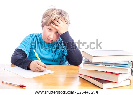 Young boy at a desk hand on his head frustrated doing homework. isolated on white with paper, books and desk. Copy space for your text - stock photo