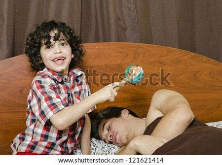 Young boy awakes his brother by making noises - stock photo