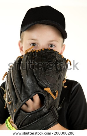 young boy baseball pitcher peering over glove - stock photo