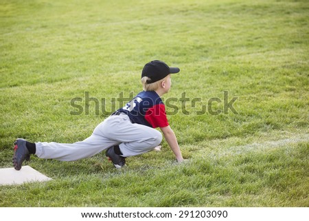 Young boy baseball player waiting on third base. He showing a funny sprinters stance - stock photo