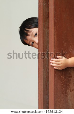Young boy behind wooden wall - stock photo