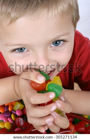 Young boy being with a table full of colorful sweets - stock photo