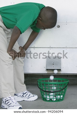 Young boy bending forward looking at a golf ball vending machine at a golf course - stock photo