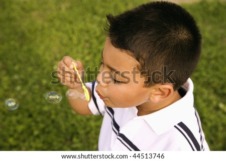 Young boy blowing bubbles outside. Horizontally framed shot. - stock photo