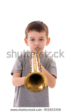 young boy blowing into a trumpet against white background - stock photo