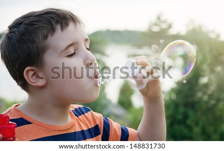 Young boy blowing soap bubbles in summer evening sunlight with green nature background