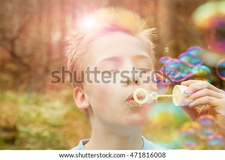 Young boy blowing soap bubbles outdoors in a garden or woodland with a bright sun flare back lighting him and iridescent bubbles floating in the air