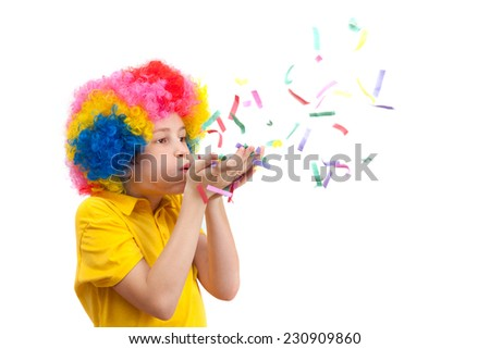 Young boy blows out confetti, isolated on white background - stock photo