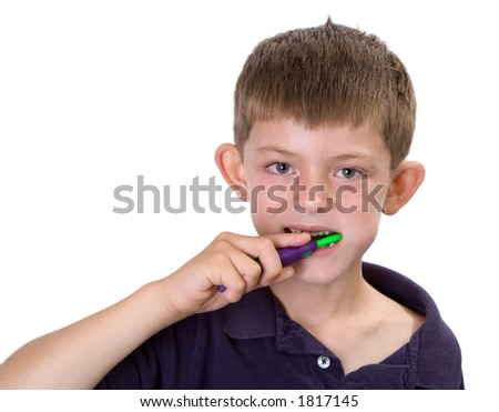 Young boy brushing his teeth while smiling. Isolated on white.