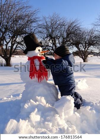 Young boy building a snowman - stock photo