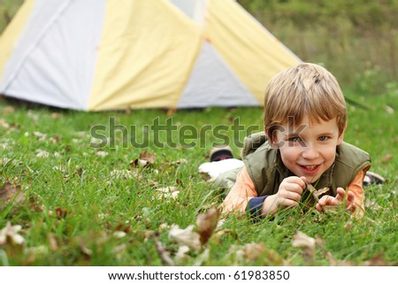 Young boy camping with tent - stock photo