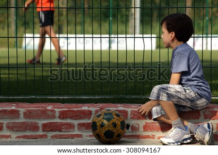 Young boy child watching organized youth soccer or football game for grid