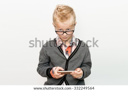 young boy child with touch phone on white background faces cheeky - stock photo