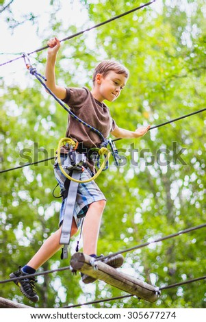 Young boy climbing in adventure rope park in safety equipment - stock photo