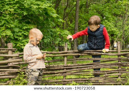 Young boy climbing over a rustic wooden fence in rural woodland as his friend stands waiting for him on the other side - stock photo