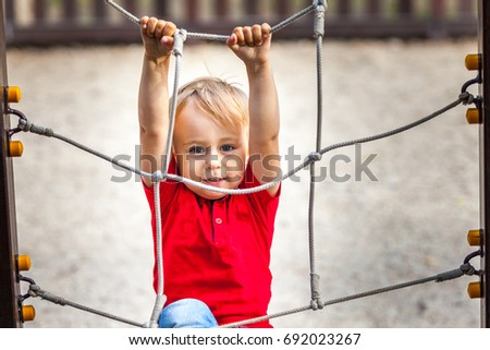 Young boy climbing rope obstacle on kid playground