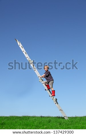 Young boy climbs a ladder on green meadow with blue sky - stock photo