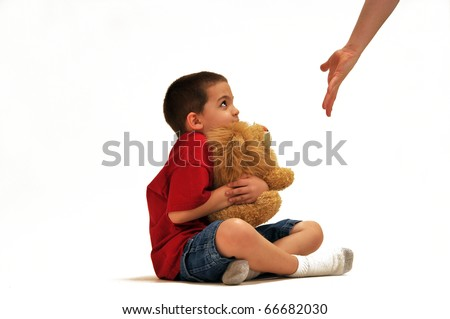 Young boy clutching his stuffed lion toy while it's about to be taken away from him. - stock photo