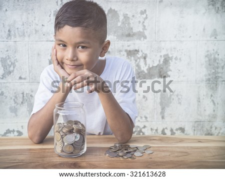 Young boy counting his saved coins and thinking about what he can buy - stock photo