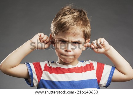 Young boy covering ears against gray background - stock photo