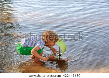 Young boy crouches down in shallow calm lake water and blows on the sail of his homemade sailing boat. It is summertime. - stock photo