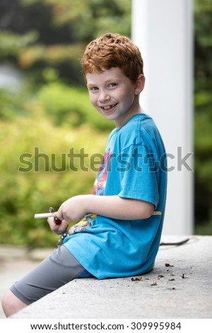 Young boy cutting a stick with a pocket knife