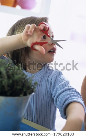 Young boy cutting herbs in kitchen