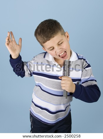 Young boy dancing and singing into a hair brush pretending to be a rock star. - stock photo